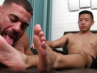 Asian dude watches as his toes are lavished