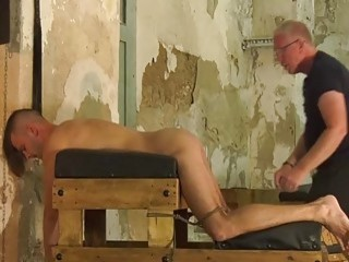 Restrained twink has his dick stroked during gay BDSM play