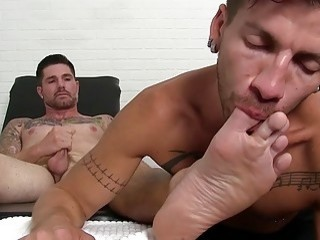 Hunk jerks off while having his feet and toes worshiped