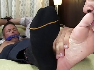 Tied up businessman has his bare feet licked and sucked