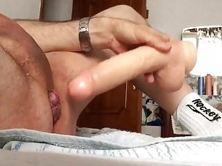 Naked man works a fake dong deep into his behind